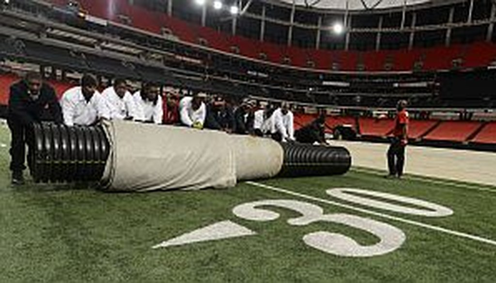 Work crews cover the playing field with a tarp in preparation for a Monster Truck event at the Georgia Dome earlier this month. Negotions are ongoing to replace the Dome with a proposed new $1 billion retractable-roof stadium.