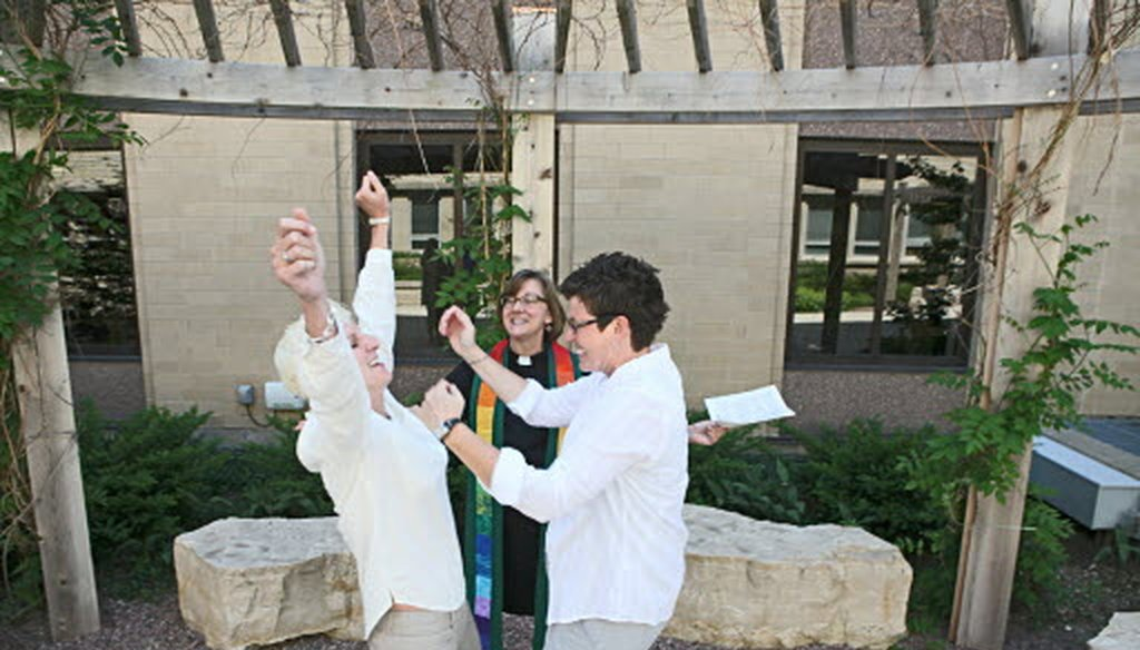 Rev. Suzelle Lynch of Unitarian Universalist Church West in Brookfield marries Karen Wells (right) and Kristie Erickson (left) of Waukesha, in a ceremony in the courtyard outside the Waukesha County Courthouse on June 9, 2014. JS photo/Mike Sears