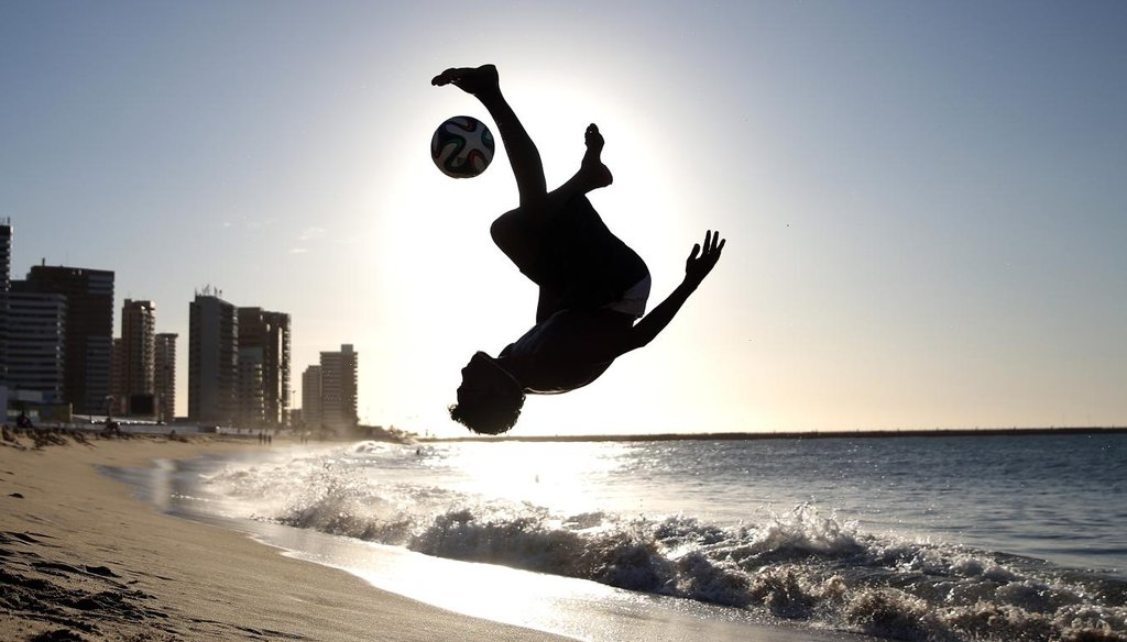 A boy plays soccer on Iracema Beach in Fortaleza, Brazil, on the eve of the 2014 FIFA World Cup. Getty photo.