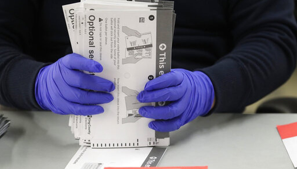 A worker wears gloves while handling ballots from the Washington state primary election, Tuesday, March 10, 2020, at the King County Elections headquarters in Renton, Wash. (AP)