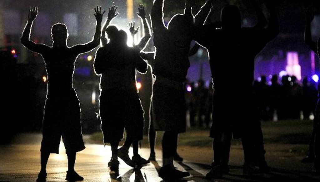 People raise their hands for advancing police wearing riot gear on Aug. 11, 2014 in Ferguson, Mo. Several nights of protests erupted in the suburb of St. Louis after a white police officer shot a black man named Michael Brown on Aug. 9. (AP photo)