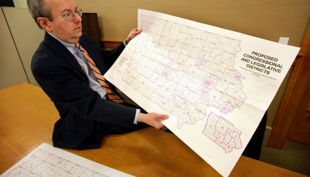 Ed Cook, legal counsel for the Iowa Legislative Services Agency, holds a map of Iowa that was used to help in drawing new congressional district lines in 2011. Three nonpartisan staffers draw district maps in Iowa. (AP Photo/Charlie Neibergall)