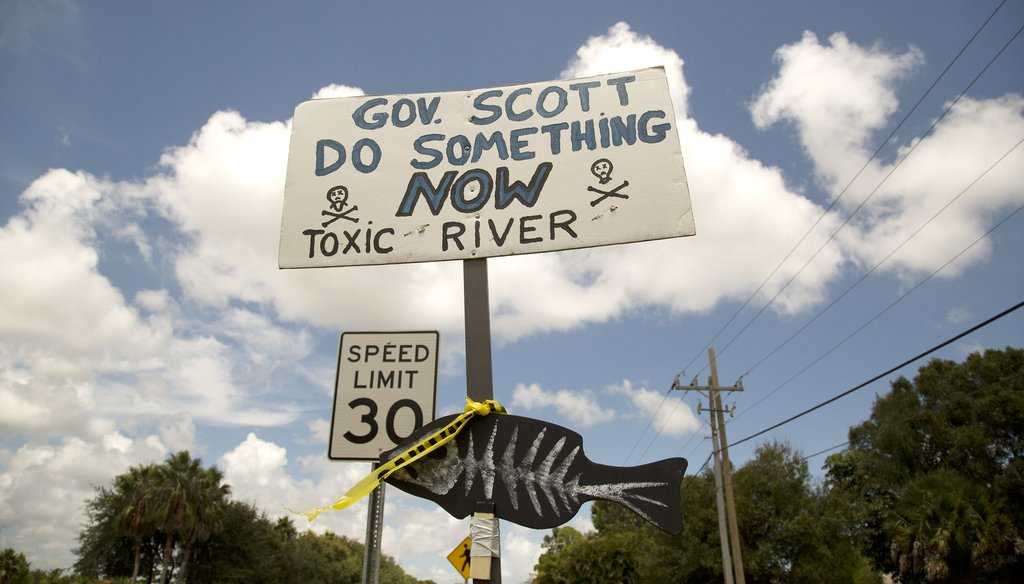 A protest sign greets Gov. Rick Scott and state Sen. Joe Negron before they tour part of the St. Lucie River near Stuart,Fla, Tuesday, Aug. 20, 2013, to access the environmental impact of water being released from Lake Okeechobee. (AP Photo/J Pat Carter)
