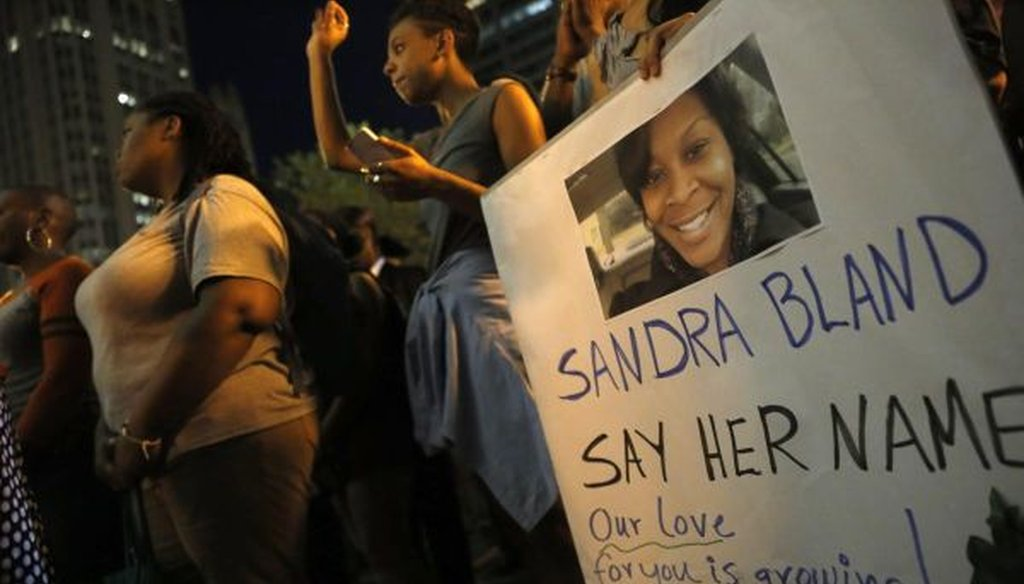 A demonstrator holds a sign for Sandra Bland during a July 28, 2015, vigil in Chicago. Bland died in a Texas county jail after a traffic stop that escalated into a physical confrontation. (AP photo | Christian K. Lee)