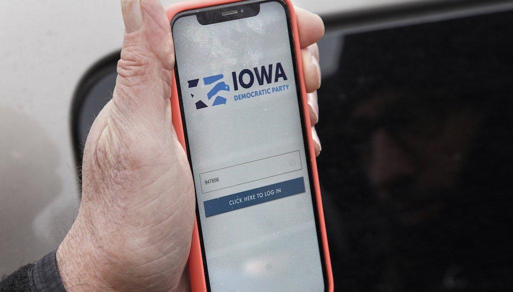 Precinct captain Carl Voss of Des Moines displays the Iowa Democratic Party caucus reporting app on his phone outside of the Iowa Democratic Party headquarters in Des Moines, Iowa, Tuesday, Feb. 4, 2020. (AP Photo/Nati Harnik)