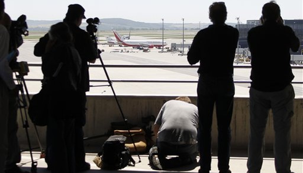 Media take pictures of a U.S., front, and a Russian plane, rear, believed to be carrying candidates for a 14-person spy swap as part of the largest spy swap since the Cold War have parked on the tarmac at Vienna's Schwechat airport, on July 9, 2010. (AP)