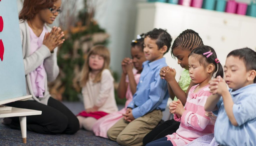 A group of children prays in this stock photo. (iStockphoto.com)