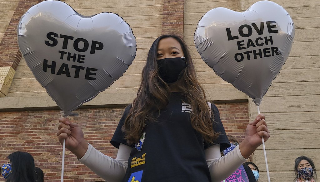 Chinese-Japanese American student Kara Chu, 18, holds a pair of heart balloons for a rally to raise awareness of anti-Asian violence outside the Japanese American National Museum in Little Tokyo in Los Angeles Saturday, March 13, 2021. (AP)