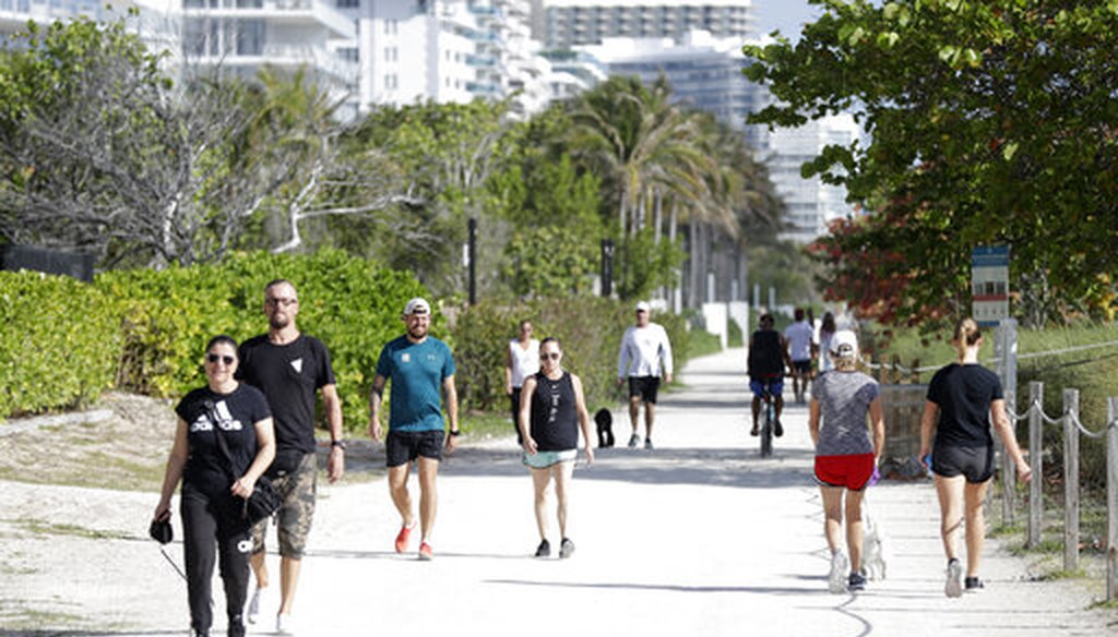 People walk their dogs and exercise on a hard-packed path along side the beach, Saturday, March 21, 2020, in Surfside, Fla. (AP)