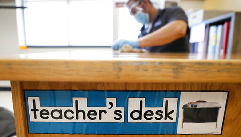 Des Moines Public Schools custodian Joel Cruz cleans a teacher's desk in a classroom at Brubaker Elementary School, Wednesday, July 8, 2020, in Des Moines, Iowa. (AP)