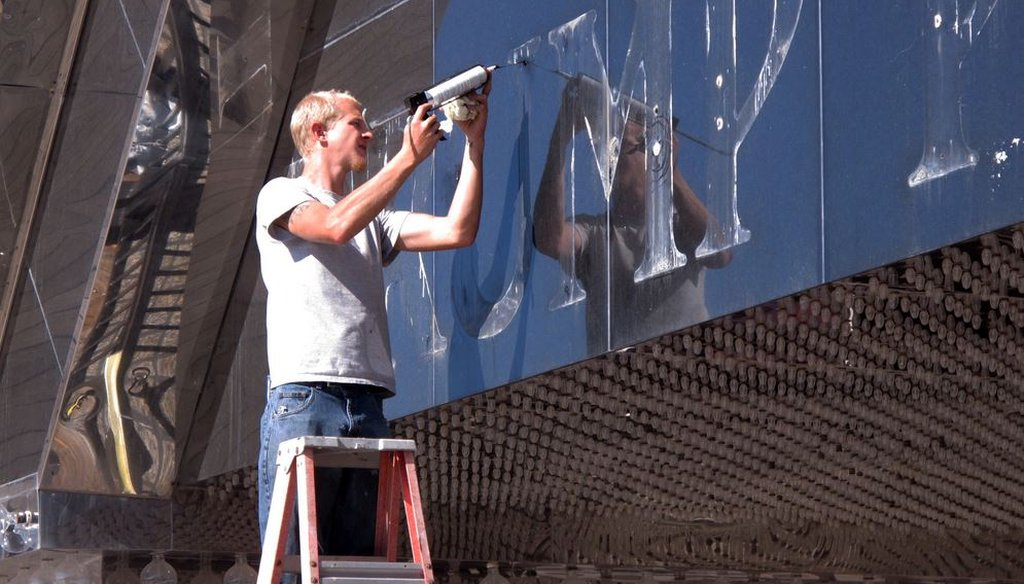 A worker applies caulk to holes in the facade of the former Trump Plaza casino in Atlantic City, N.J. after letters spelling out the casino's name were removed Oct. 6, 2014. (AP photo/Wayne Parry)