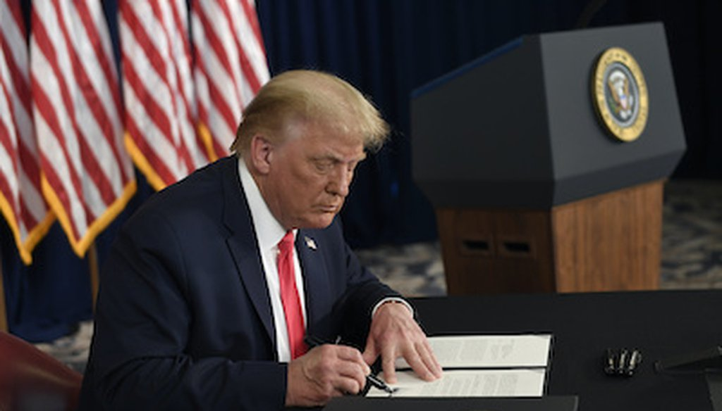 President Donald Trump signs one of four executive measures addressing the economic fallout from the COVID-19 pandemic on Aug. 8, 2020. (AP)