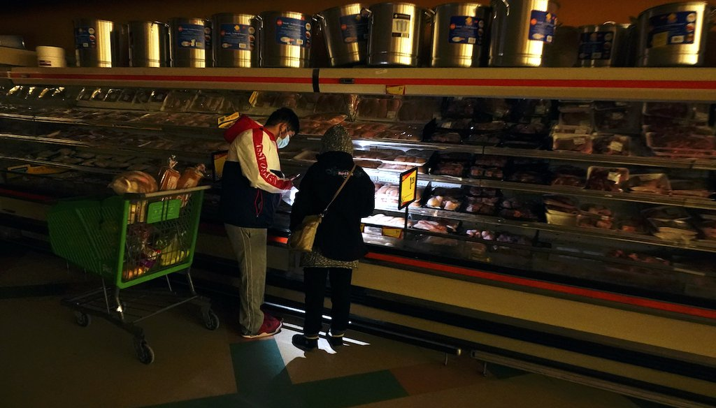 Customers use the light from a cell phone at a grocery store in Dallas that lost power during winter storms, Feb. 16, 2021. (AP)