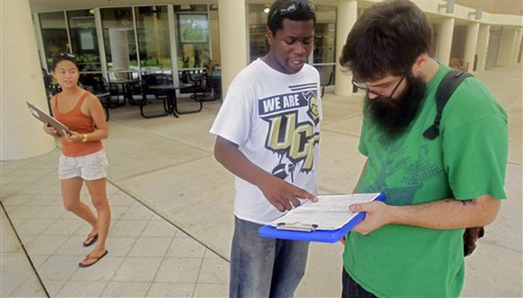 In this July 31, 2012, photo, Aubrey Marks, left, watches Jordan Allen, center, as he helps student Casey Eirhstaedt, right, register to vote at the University of Central Florida in Orlando, Fla. (AP)