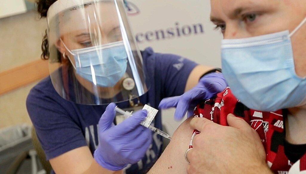 ER nurse Stephanie Fidlin, left, administers a COVID-19 vaccine to Jim Gruenewald, an Ascension Wisconsin ICU nurse at Ascension SE Wisconsin Hospital in Franklin on Dec. 16, 2020 (Mike De Sisti / Milwaukee Journal Sentinel).