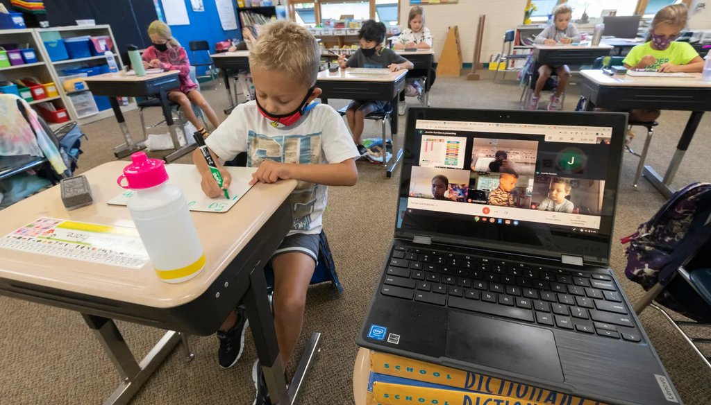 Second grade student Mason Fiore does classwork while next to a laptop with images of students working at home Sept. 4, 2020 at Lake Country School in Hartford. (Mark Hoffman/Milwaukee Journal Sentinel).