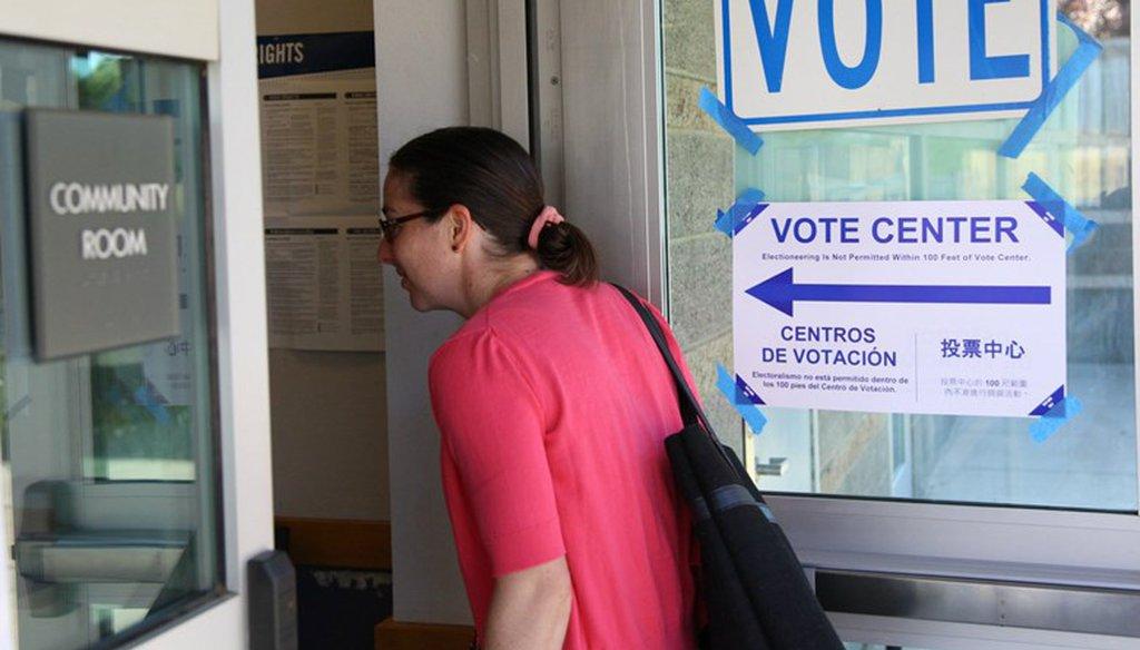 A woman in Sacramento, Calif. drops off her ballot at a vote center. Andrew Nixon / CapRadio