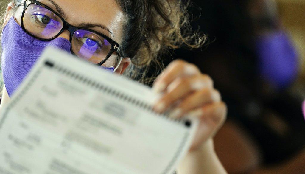 A Georgia election worker examines ballots at State Farm Arena Nov. 5, 2020, in Atlanta. (AP)
