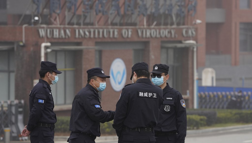Security personnel gather near the entrance of the Wuhan Institute of Virology during a visit by the World Health Organization team in Wuhan in China's Hubei province, Feb. 3, 2021. (AP)