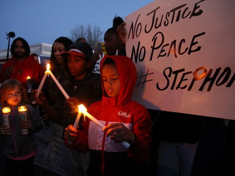 Children light candles at a vigil for Stephon Clark in South Sacramento. Andrew Nixon / Capital Public Radio