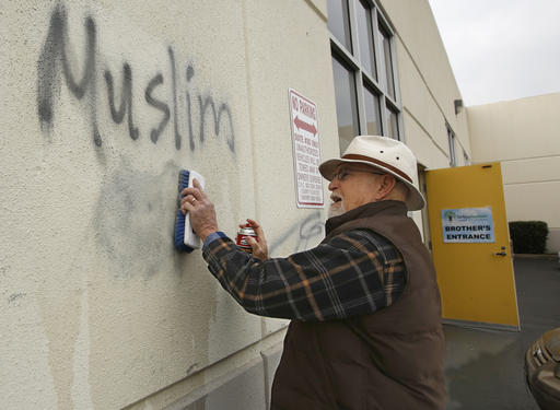 Tom Garing cleans up racist graffiti painted on the side of a mosque in what officials are calling an apparent hate crime, Wednesday, Feb. 1, 2017, in Roseville, Calif. (AP Photo/Rich Pedroncelli)