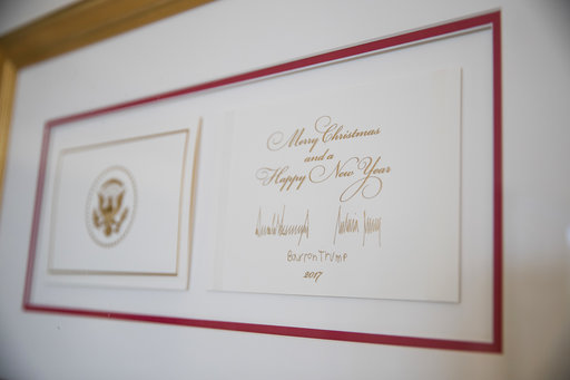 The official White House Christmas card signed by President Donald Trump, first lady Melania Trump, and their son Barron Trump at the White House, Nov. 27, 2017. (AP Photo/Carolyn Kaster)