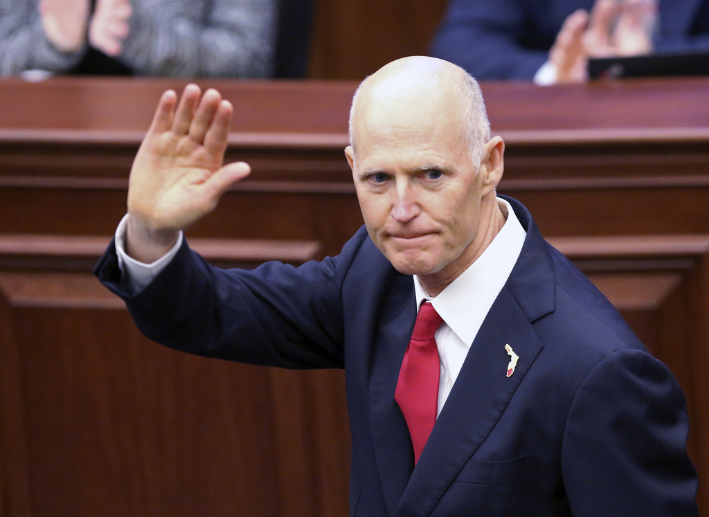 Gov. Rick Scott waves as he is introduced to the Senate on the first day of legislative session, Tuesday, Jan. 9, 2018, in Tallahassee, Fla. (AP Photo/Steve Cannon)