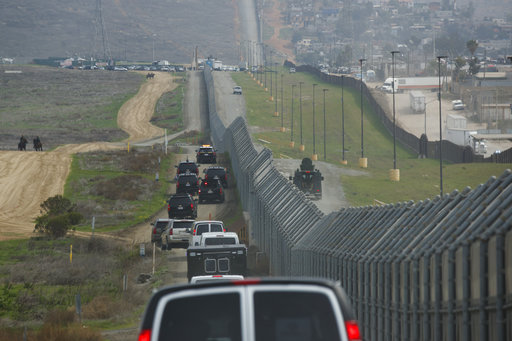 A motorcade carrying President Donald Trump drives along the border before look at border wall prototypes, Tuesday, March 13, 2018, in San Diego. (AP Photo/Evan Vucci)