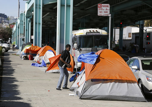 A man stands outside his tent in San Francisco in 2016 in a neighborhood with many homeless people. (AP)
