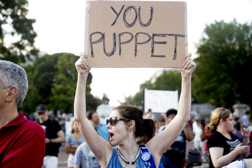"A woman holds a sign that reads ""You Puppet"" during a protest outside the White House on July 17, 2018. (AP/Andrew Harnik)"