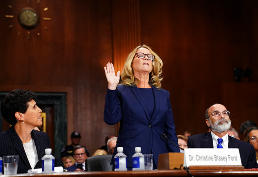 Christine Blasey Ford is sworn in to testify before the Senate Judiciary Committee on Capitol Hill in Washington, Thursday, Sept. 27, 2018. Her attorney's Debra Katz and Michael Bromwich watch. (AP Photo/Andrew Harnik, Pool)