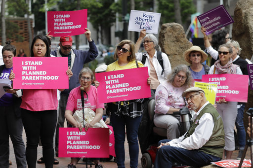 Protesters hold signs supporting Planned Parenthood in Seattle on July 10, 2018. (AP/Ted S. Warren)