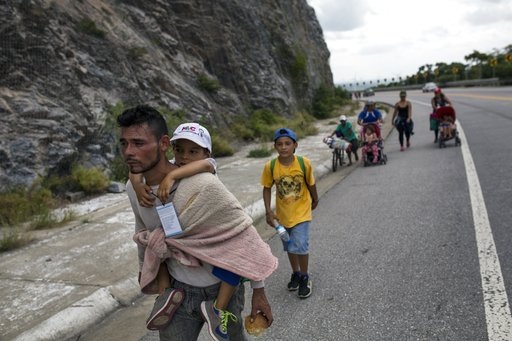 Honduran migrant Jose Macy carries his four-year-old nephew Yair Perez as the thousands-strong caravan of Central Americans migrants hoping to reach the U.S. border moves onward from Juchitan, Oaxaca state, Mexico, on Thursday, Nov. 1, 2018. (AP)