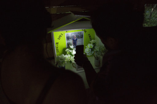 Neighbors illuminate a memorial of Jakelin Caal Maquin at her grandfather's house in San Antonio Secortez, Guatemala, Sunday, Dec. 23, 2018. (AP Photo/ Oliver de Ros)
