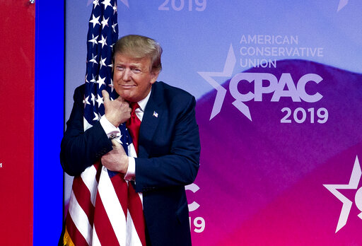 President Donald Trump hugs the American flag as he arrives to speak at Conservative Political Action Conference on March 2, 2019. (AP)