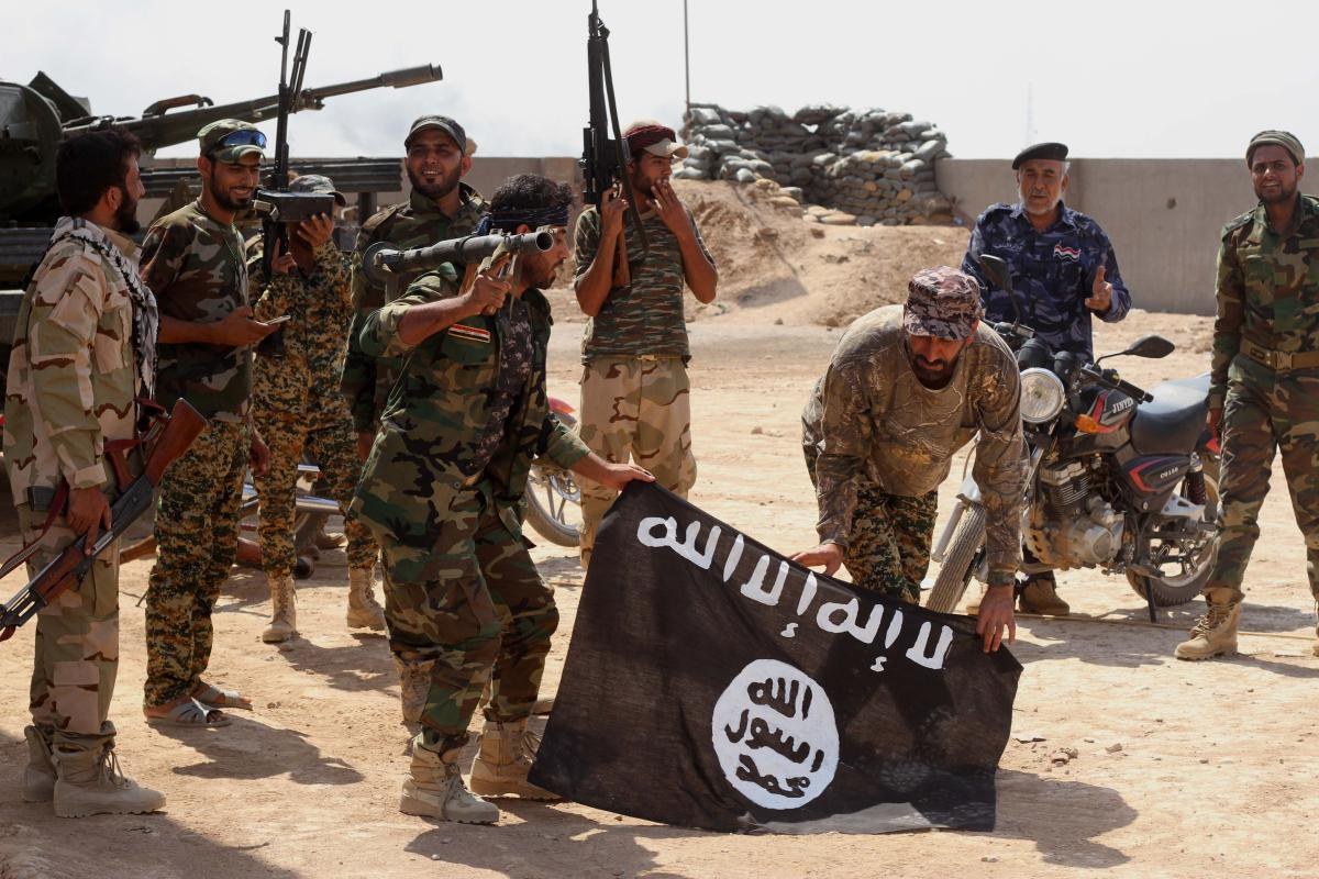 Iraqi security forces hold a flag of the Islamic State group they captured during an operation outside Amirli, some 105 miles north of Baghdad, Iraq, Sept. 1, 2014. (AP)