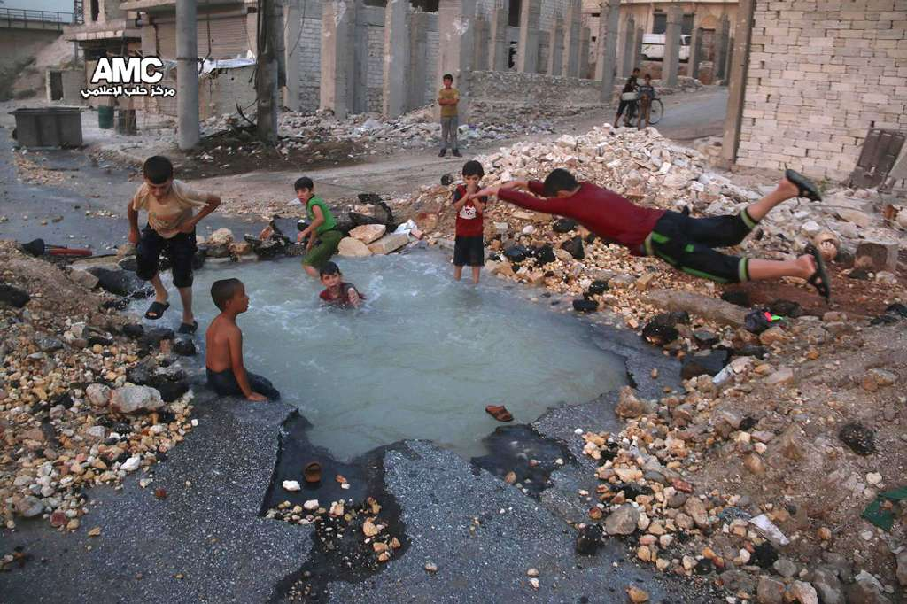 This Aug. 31, 2016 photo, provided by the Syrian anti-government activist group Aleppo Media Center (AMC), shows Syrian boys dive into a hole filled with water that was caused by a missile attack in the rebel-held neighborhood of Sheikh Saeed in Aleppo.