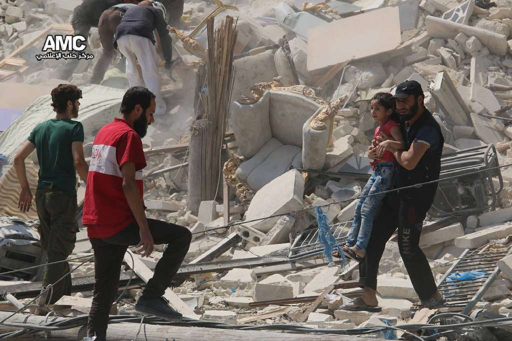 This photo provided by the Syrian anti-government activist group Aleppo Media Center (AMC), shows a Syrian man carrying a girl away from the rubble of a destroyed building after barrel bombs were dropped on the Bab al-Nairab neighborhood in Aleppo, Syria.