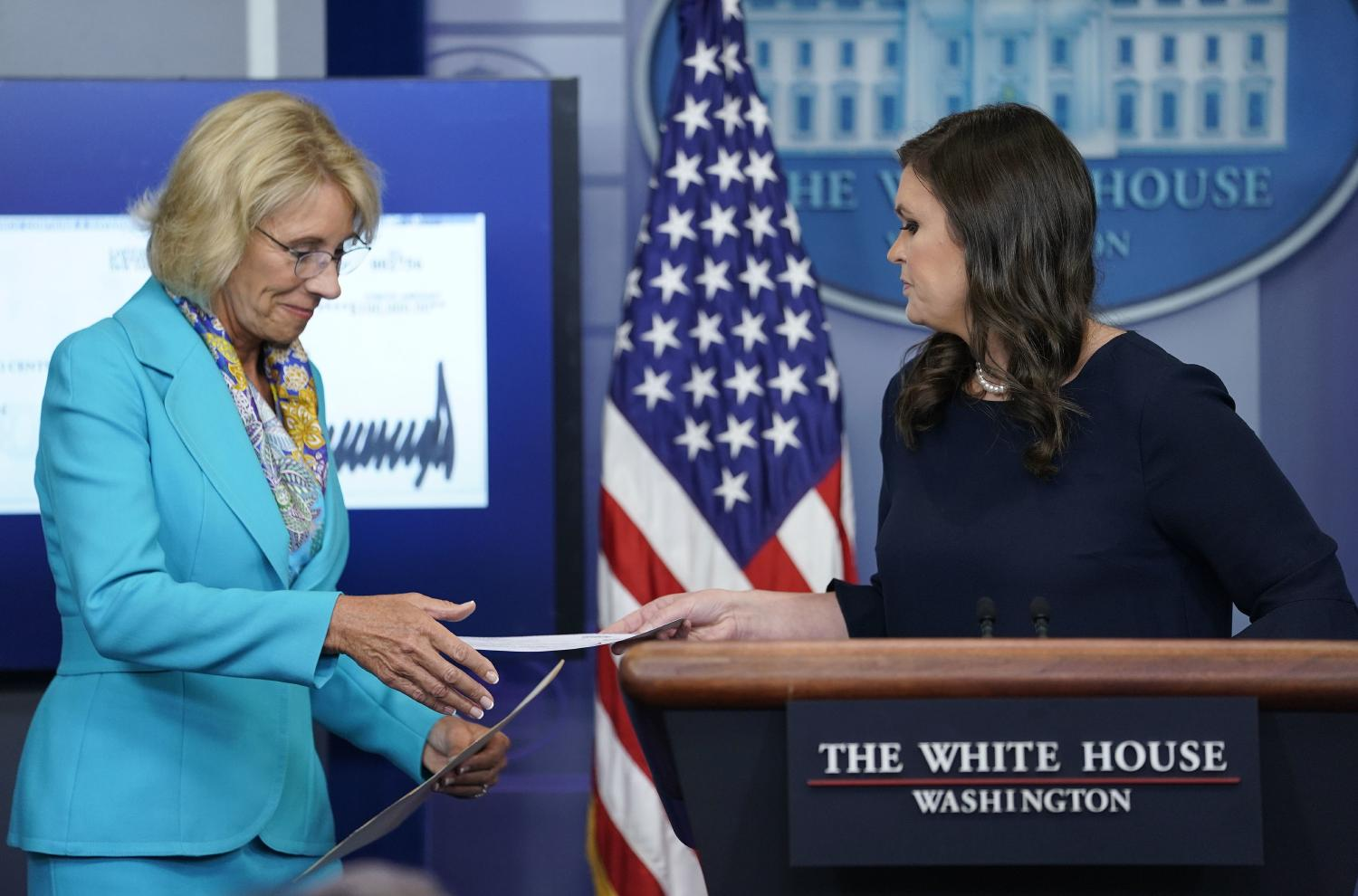 White House press secretary Sarah Huckabee Sanders, right, hands Education Secretary Betsy DeVos, left, a check signed by President Donald Trump in the Brady Press Briefing room of the White House in Washington, Wednesday, July 26, 2017. (AP)