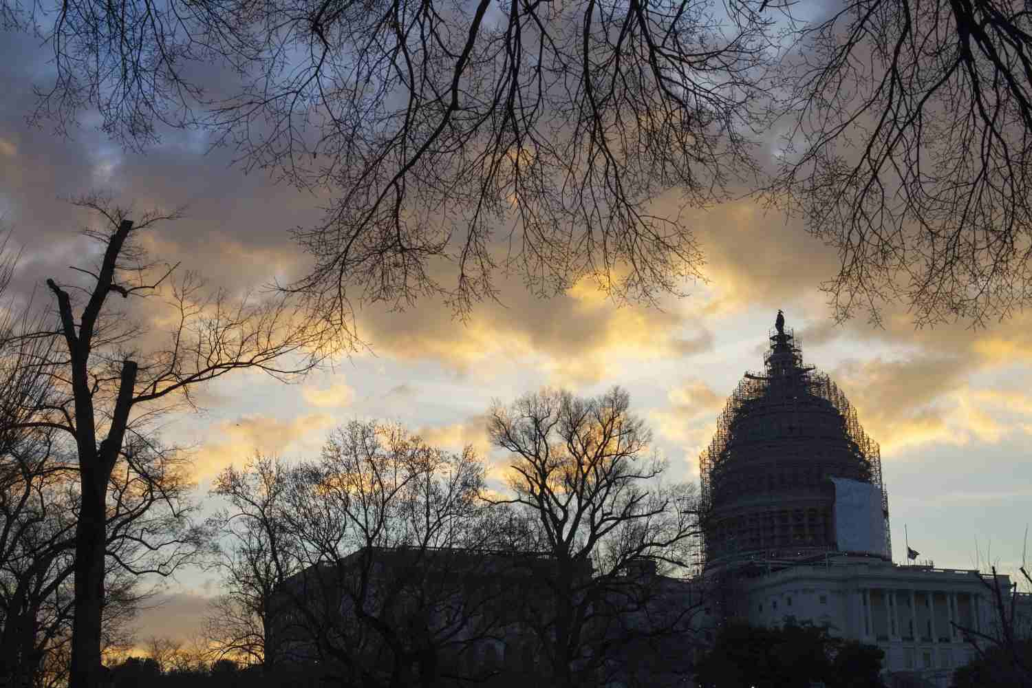 The sun rises over the Capitol, covered in scaffolding for repairs, in Washington on Jan. 5, 2015.