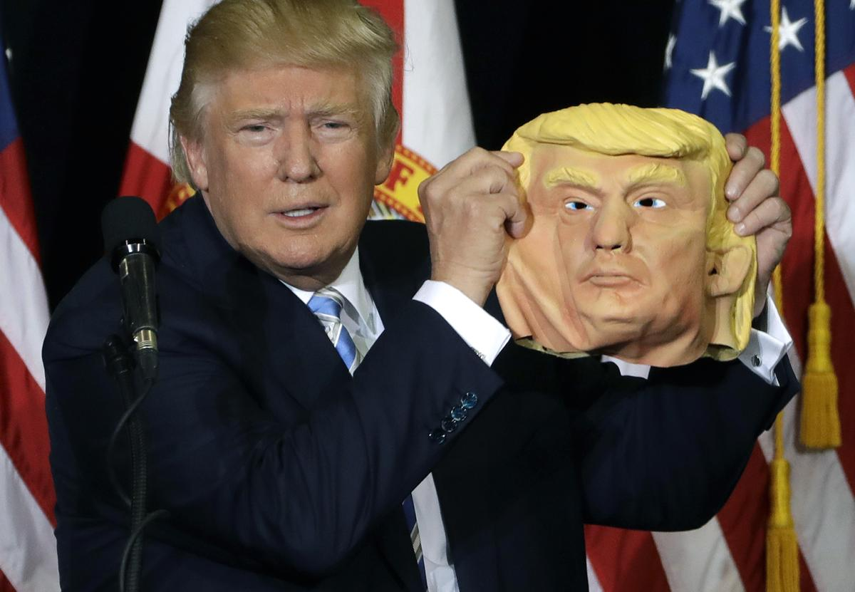 Republican presidential candidate Donald Trump holds up a Donald Trump mask during a campaign speech, Monday, Nov. 7, 2016, in Sarasota, Fla. (AP Photo/Chris O'Meara)