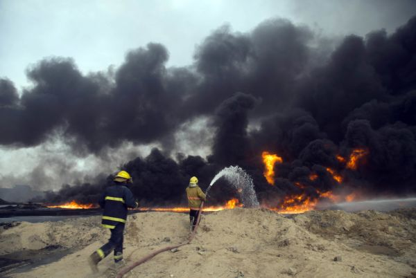 Iraqi firefighters battle a large fire at oil wells in Qayara, Iraq, on Aug. 31, 2016. (AP)