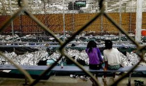 Two girls watch a World Cup soccer match from their holding area in Nogales, Ariz., where hundreds of mostly Central American immigrant children are being processed and held.