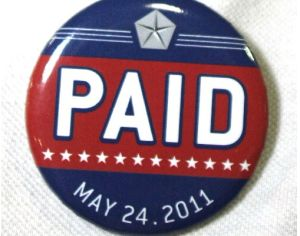 """A Chrysler assembly line worker sports a pin labled """"PAID"""" on his shirt before Chrysler Group announced the repayment of the remainder of its loans from the U.S. Government."""