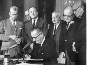 President Lyndon Johnson signs the Civil Rights Act. Also pictured are Sen. Everett Dirksen (left) and Reps. Charles Halleck and William McCulloch, all Republicans.