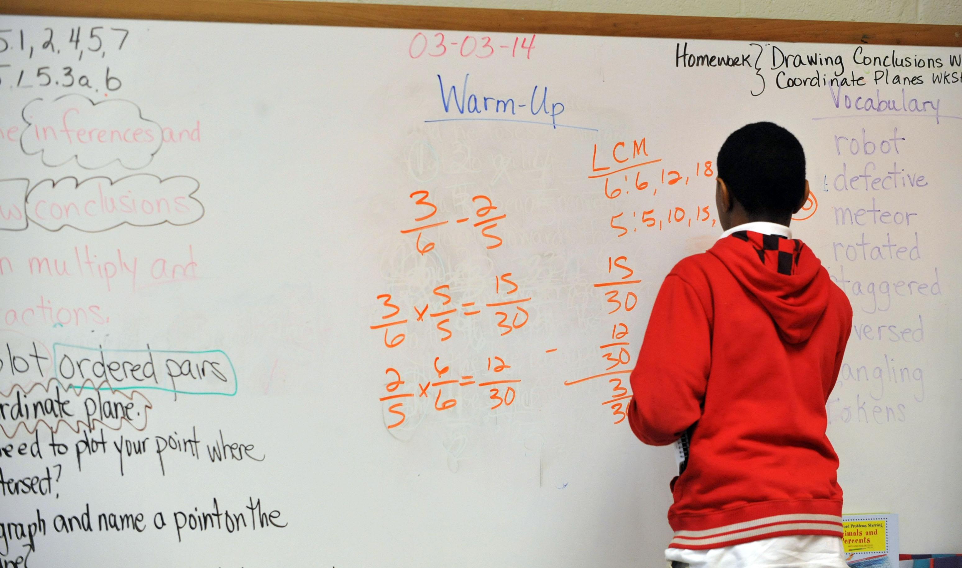 Fifth-grade student Tracey Bridges works a problem on the board at Venetian Hills Elementary School Monday, March 3, 2014. KENT D. JOHNSON / KDJOHNSON@AJC.COM