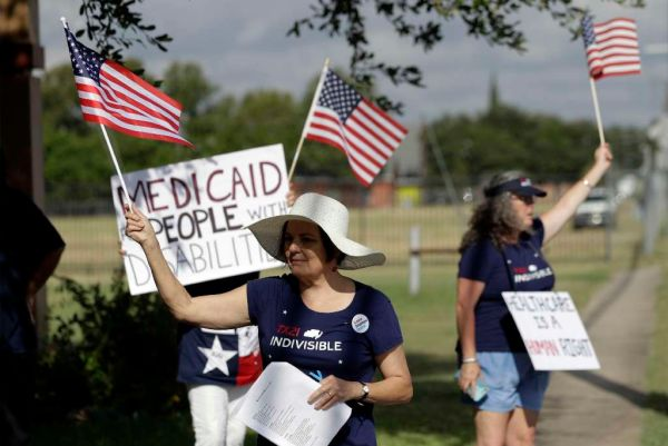 Protesters stand outside of a radio station where Sen. Ted Cruz, R-Texas, stopped for a radio interview on July 6, 2017, in advance of a town hall where a Republican health care bill was to be discussed. (AP/Eric Gay)