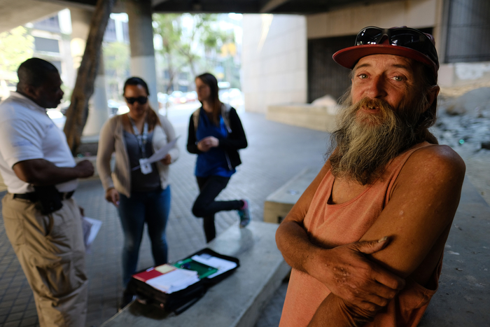 In this Friday, June 17, 2016 photo, homeless man David Brophy, right, talks to People Assisting The Homeless (PATH) outreach team members who are helping him acquire an ID card on a street near where he lives in Los Angeles. (AP Photo/Richard Vogel)