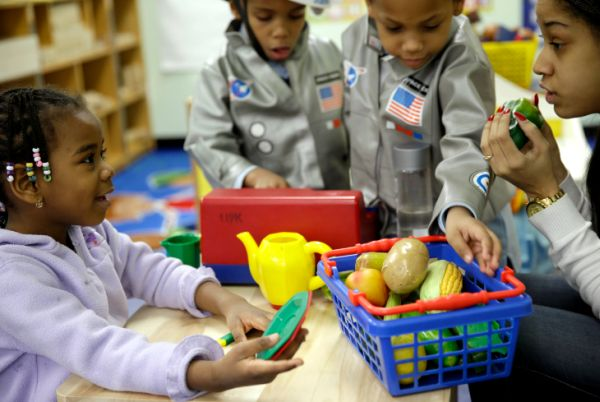 Oumou Balde, 4, left, plays with her teacher, Jacqualine Sanchez, right, and some pretend food in a pre-kindergarten class at the Sheltering Arms Learning Center in New York in a program to educate children about nutrition and health. (Associated Press)