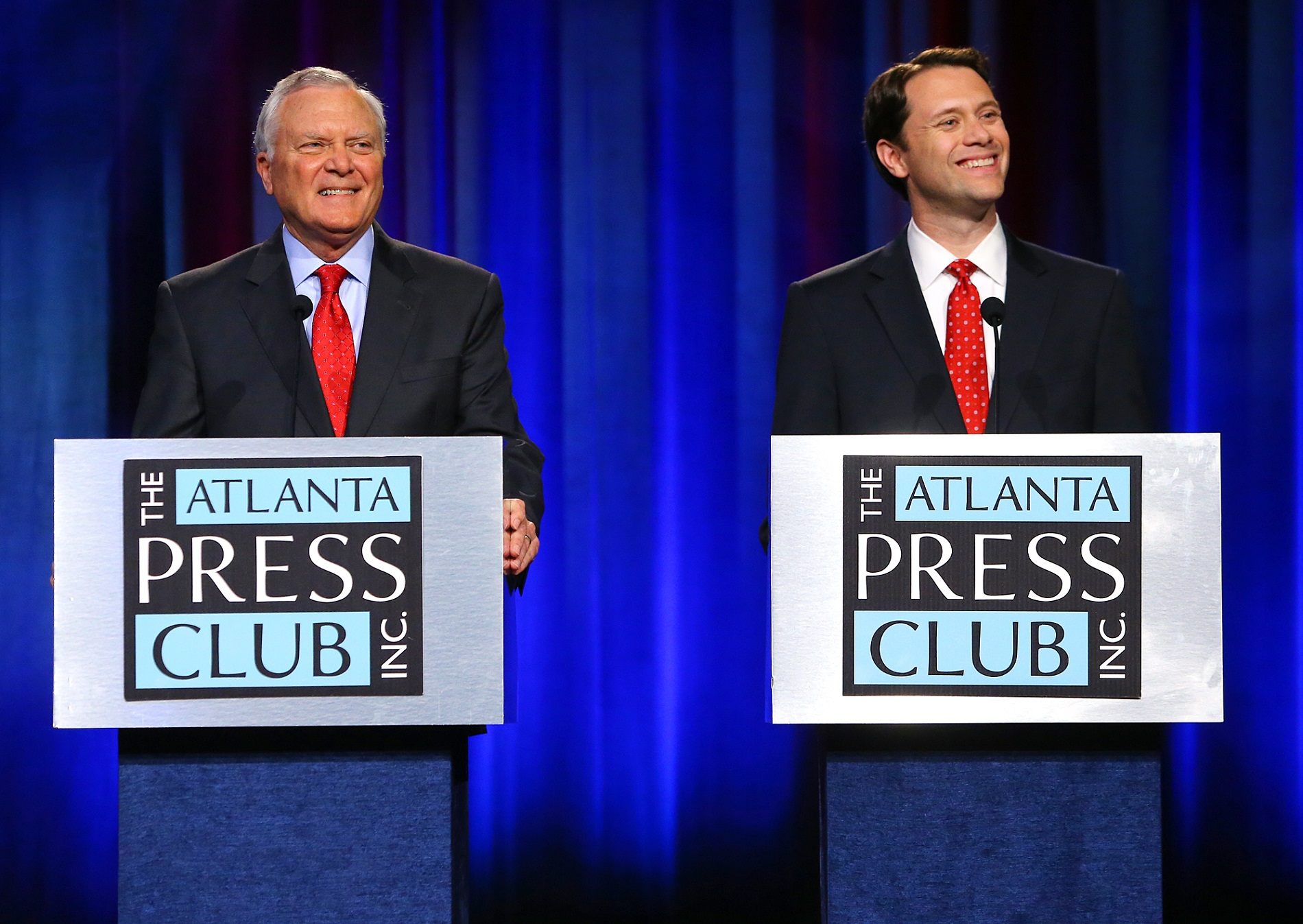 Republican Gov. Nathan Deal, left, and his Democratic rival, state Sen. Jason Carter, smile at a question during the Atlanta Press Club debate on Oct. 19. CURTIS COMPTON PHOTOS / AJC